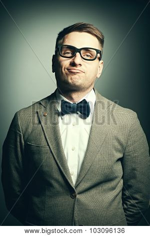 Confident nerd in eyeglasses and bow tie against grey background