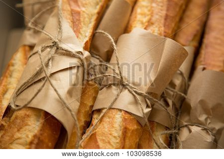 Loafs of French baguette bread tied together with paper and string