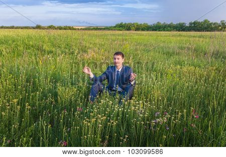 businessman is meditating in the nature.