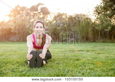 Young woman stretching outside in the grass