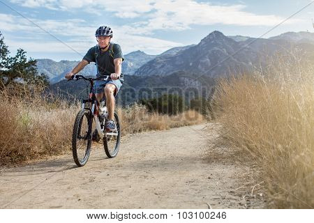 Man mountain biking wearing a water backpack