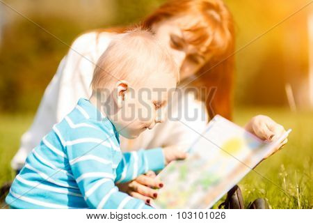 Picture of beautiful woman with son sitting down on green grass field and read fairytale in park
