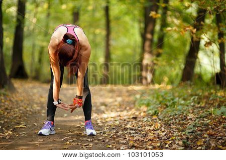 young fit woman doing exercise in park, rear view
