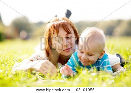 Cute boy and young woman laying on grass in park