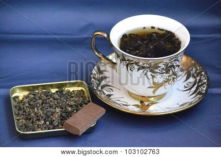 tea cup and saucer white with gold okaemkoy, with a piece of chocolate and brewing tea on a blue bac