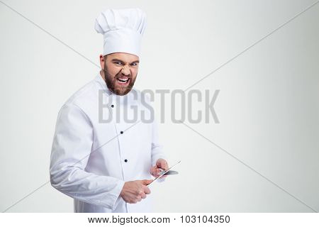 Portrait of a funny male chef cook sharpening knife isolated on a white background