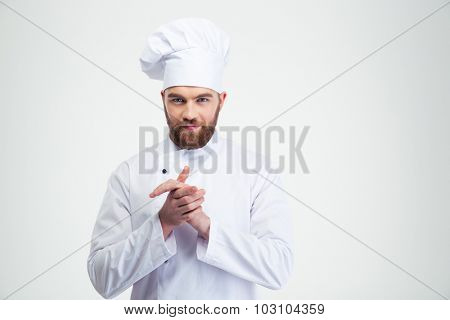 Portrait of a happy male chef cook standing isolated on a white background and looking at camera