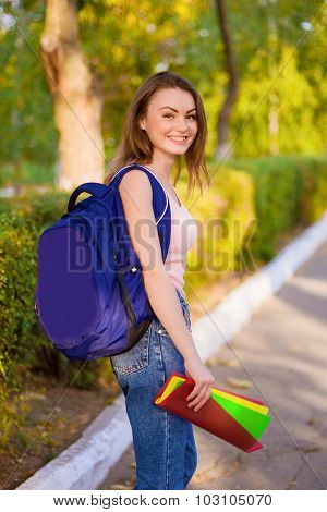 A girl student with a backpack in park