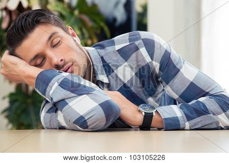 Portrait of a casual man sleeping at the table at home