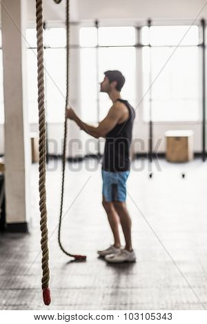Young bodybuilder holding the ropes in crossfit gym