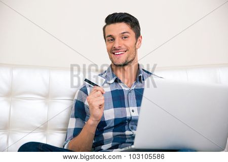 Portrait of a happy man sitting on the coach with bank card and laptop at home