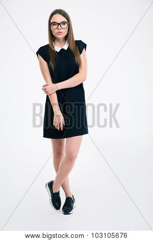 Full length portrait of a beautiful woman in glasses and dress standing isolated on a white background