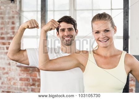 Portrait of couple flexing muscles in crossfit gym