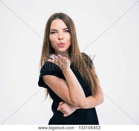 Portrait of a young cute woman blowing kiss at camera isolated on a whiet background