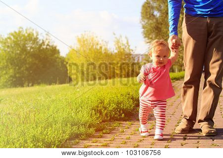 first steps of little girl with dad in the park