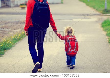 Mother holding hand of little daughter with backpack