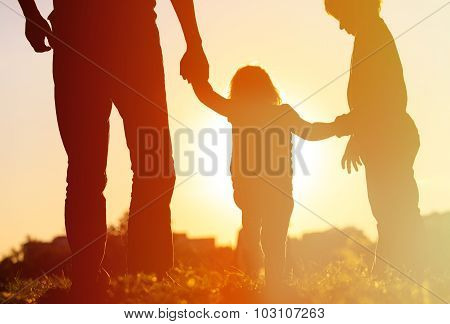 Silhouette of father with two kids walking at sunset