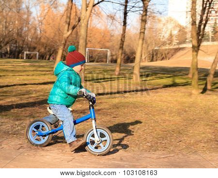 little boy riding runbike in autumn park