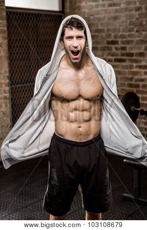 Portrait of muscular man wearing hood at the gym