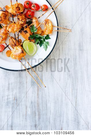 Healthy chicken kebabs served with tomatoes lime and coriander on a rustic enamel plate, copy space
