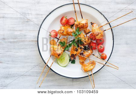 Healthy chicken kebabs served with tomatoes lime and coriander on a rustic enamel plate