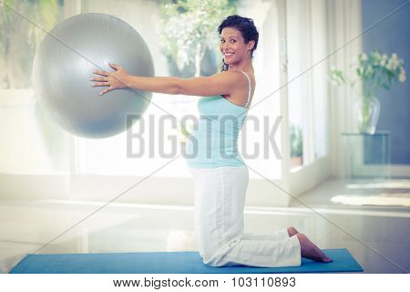 Full length portrait of smiling pregnant woman holding exercise ball at fitness studio