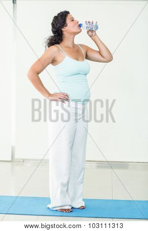 Full length of pregnant woman drinking water from bottle in fitness studio