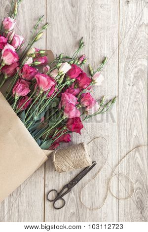 Pink eustoma flowers wrapped in craft paper, twine and vintage scissors on natural wooden floor, selective focus, shabby chic style, space for custom text.