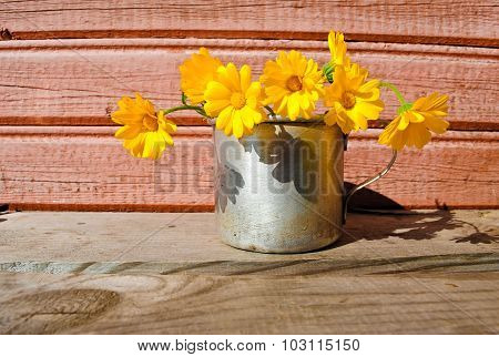 Yellow flowers on the unpainted wooden surface