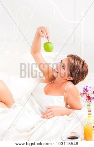 Young woman with apple in hands in bed