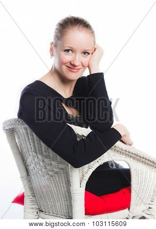 woman sits in an arm-chair on a white background