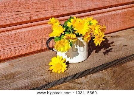 Yellow calendula on the unpainted wooden surface