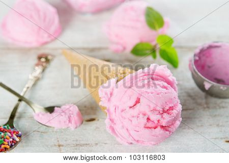 Pink ice cream in waffle cone with utensil on rustic wooden background.