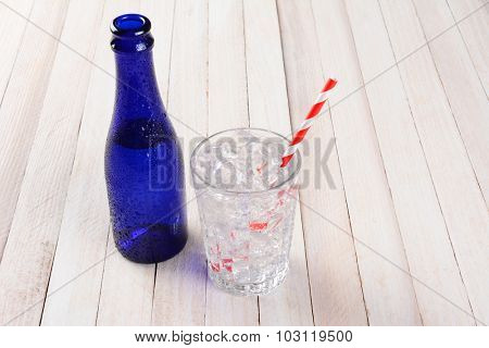 A blue bottle of water with a glass full of ice and a red and white striped drinking straw. Horizontal format on a rustic wood table.