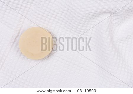 A round bar of artisanal soap on a white towel. Horizontal format with copy space.