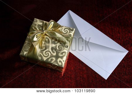 Gift in a golden box and blank envelope