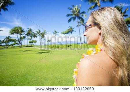 Woman enjoying a sunny Hawaiian vacation. Photo view from behind of a beautiful blond woman