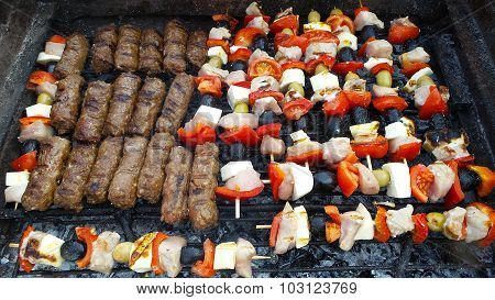Minced meat rolls and chicken skewers on the grill