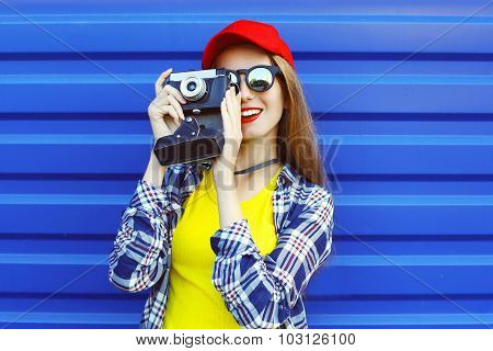 Fashion Pretty Cool Girl Wearing A Colorful Clothes With Retro Camera Shooting Over Blue Background