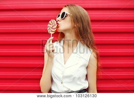 Portrait Of Pretty Young Woman With Sweet Lollipop Over Pink Background