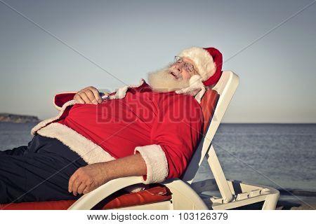 Santa Claus sleeping on a beach chair