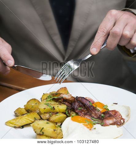 Closeup Of Man Eating Fried Eggs, Potatoes And Bacon