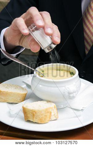Closeup Of Man Putting Salt In A Bowl Of Soup