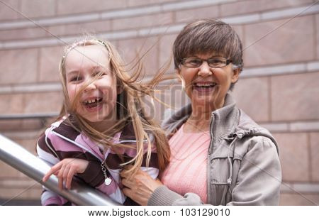 Senior lady with granddaughter outdoor portrait in the city
