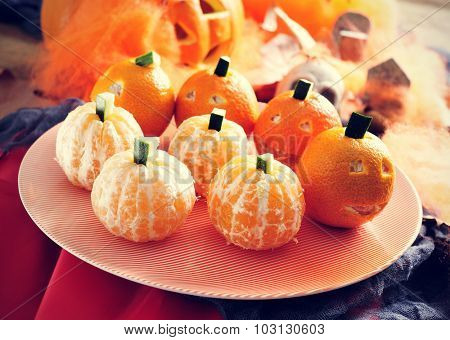 a pile of mandarines ornamented as Halloween pumpkins in a tray with and some scary ornaments in the background, such as skulls, spiders and cobwebs