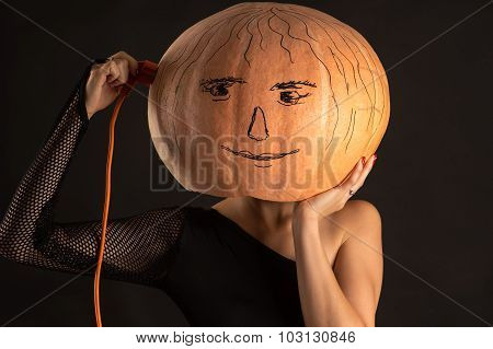 woman with a pumpkin on head and electric cord