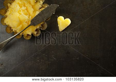 ghee or melted butter in heart shape with knife and dark metal backdrop