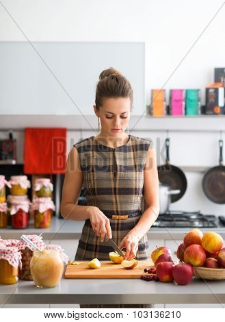 Woman Looking Down While Cutting Apples In Kitchen