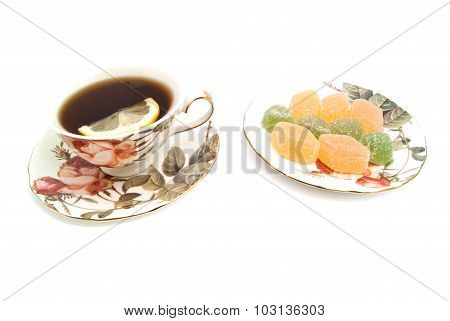 Cup Of Tea With Lemon And Fruit Candies On White
