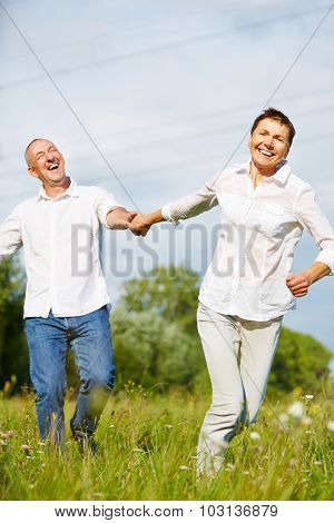 Happy senior couple running in summer over a grean meadow